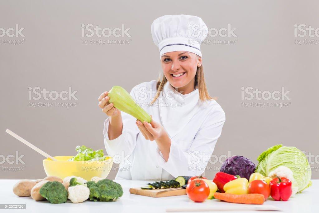 Female chef  showing zucchini stock photo