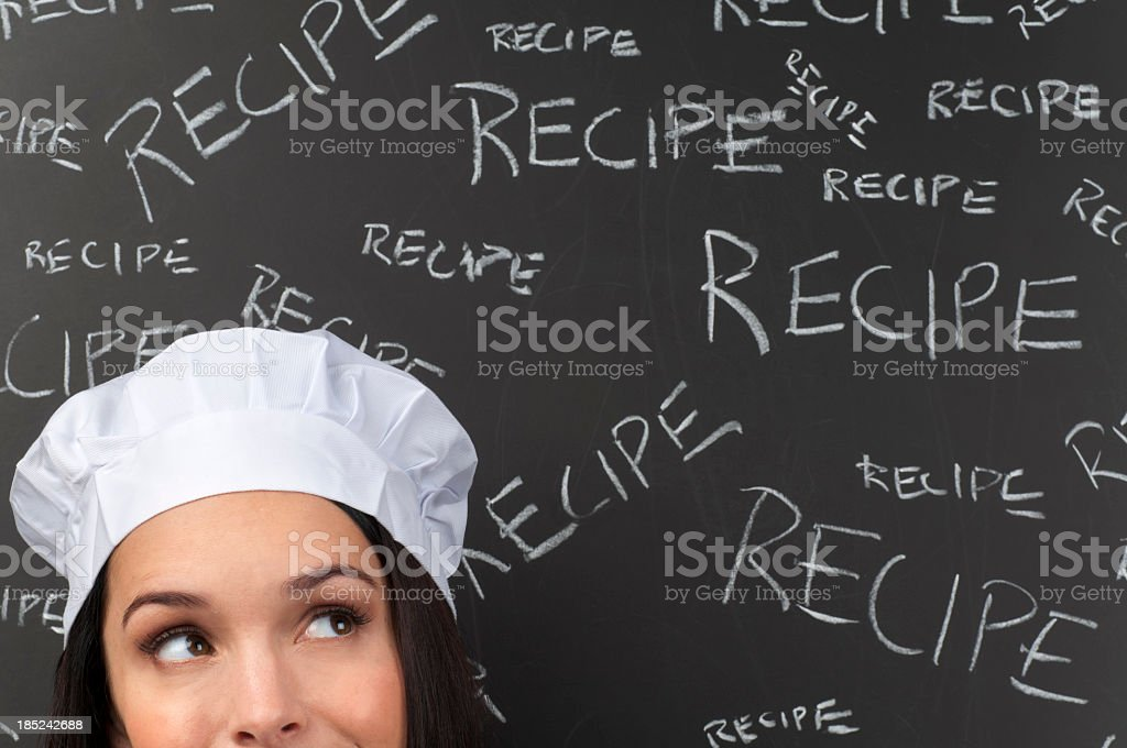 Female chef thinking in front of recipe words stock photo