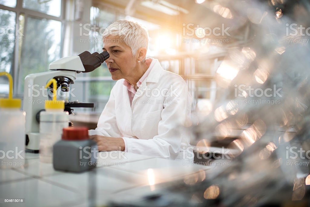 Female chemist analyzing something through a microscope in laboratory. stock photo