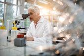 Female chemist analyzing something through a microscope in laboratory.