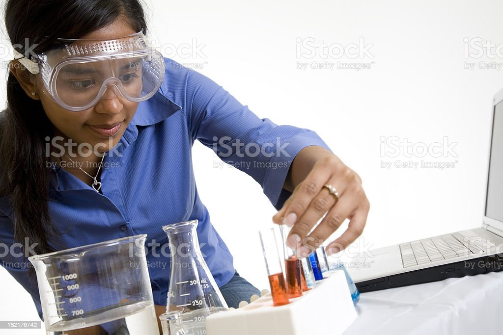 Female Chemist Looking Closely at Test Tube with Red Liquid royalty-free stock photo