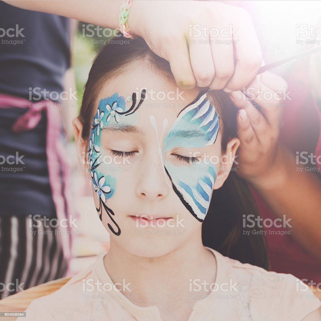 Female child face painting, making butterfly process stock photo