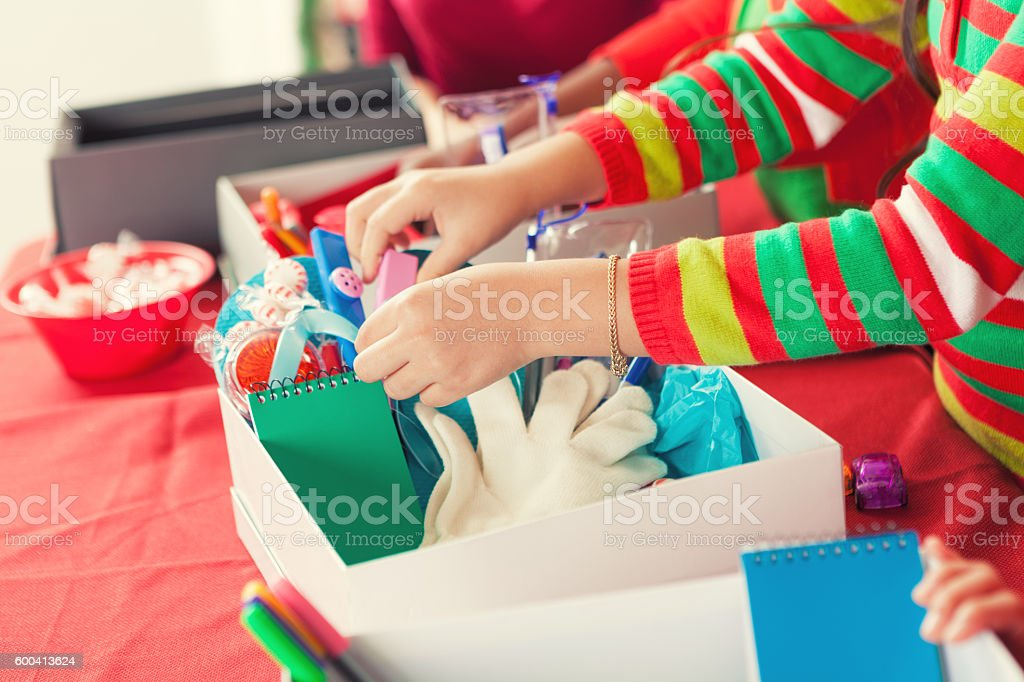 Female child filling Christmas donation boxes for children in need stock photo