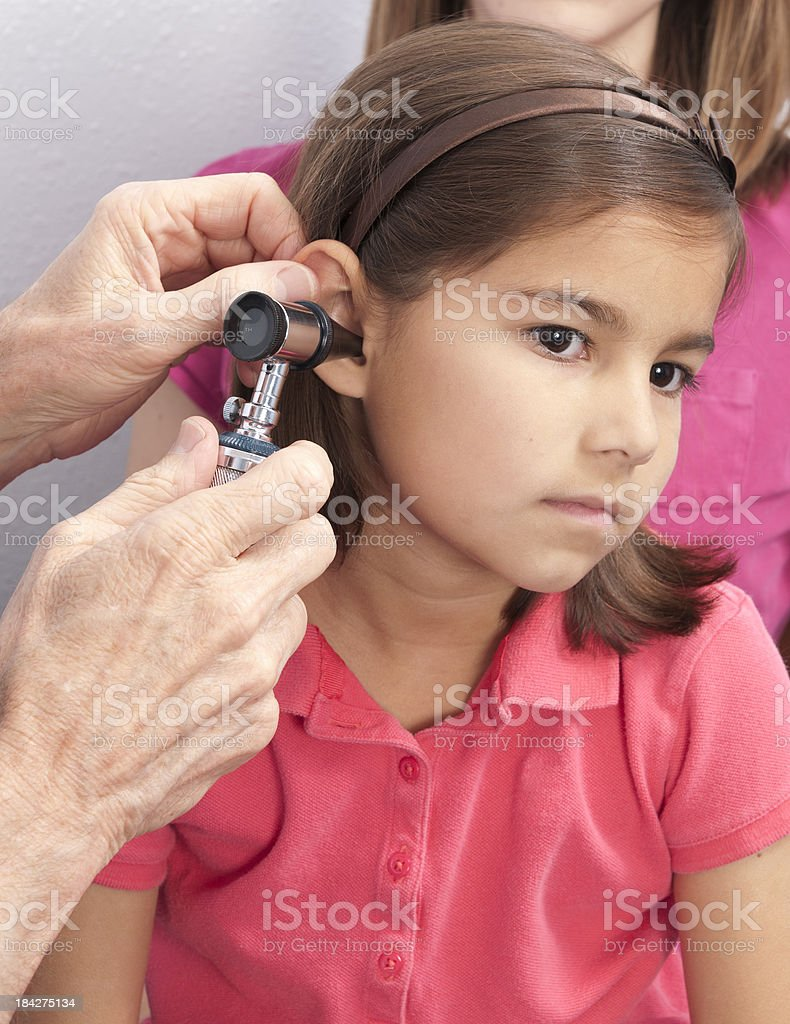 Female Child Having Ear Checked, Hands of Doctor with Otoscope royalty-free stock photo