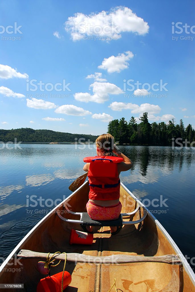A female child in the canoe in the water stock photo