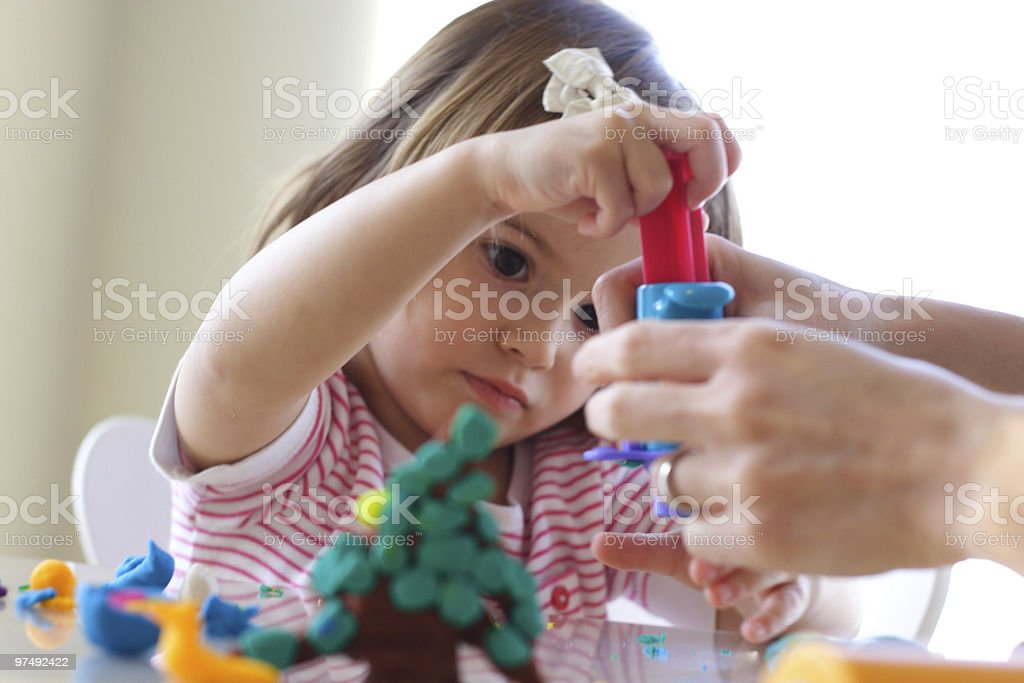 Female child using play dough with adult assistance royalty-free stock photo