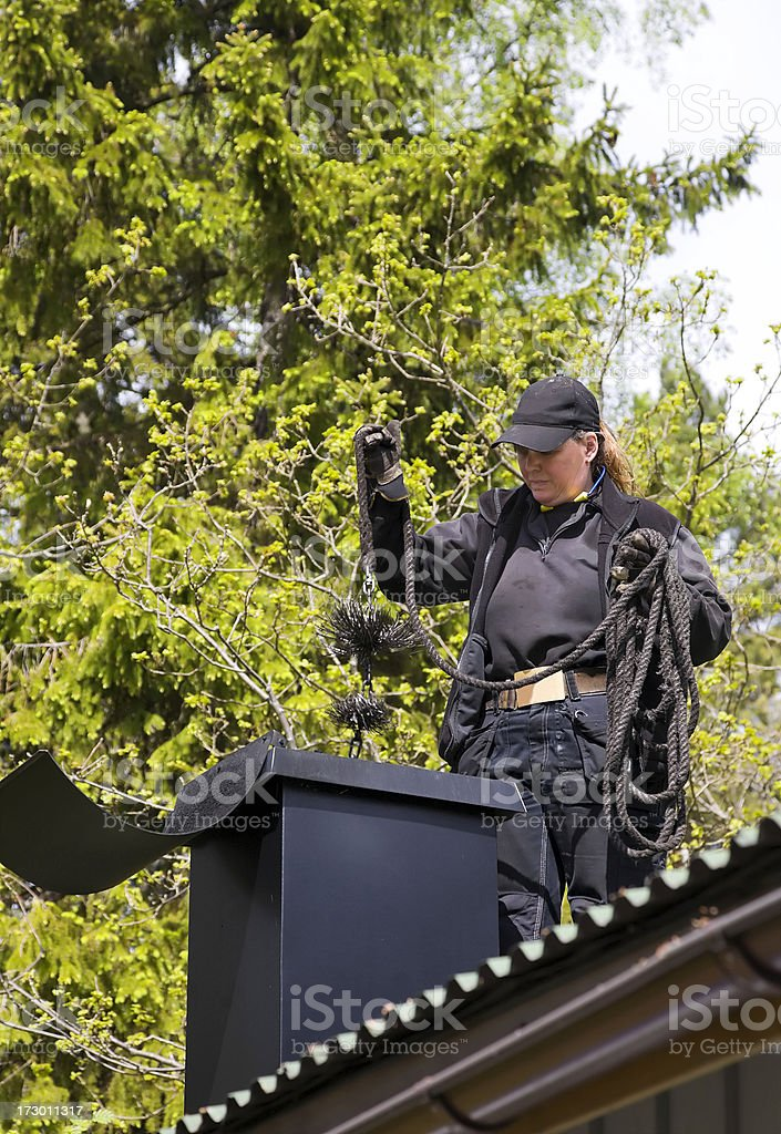 Female chimney sweeper standing on a roof working stock photo
