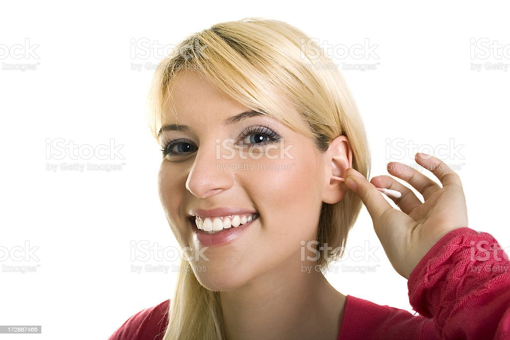 Female cleaning ear with q-tips stock photo