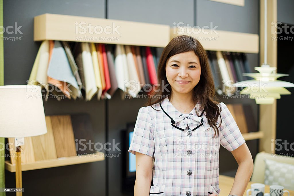 Female Clerk working in the Interior shop stock photo