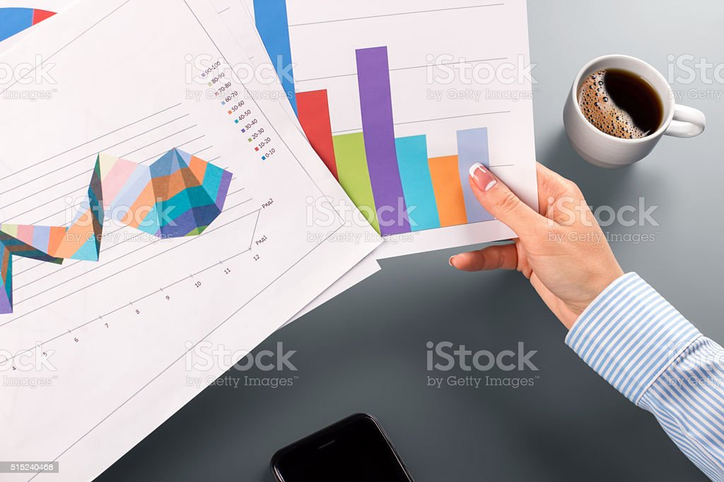 Female clerk's hands holding charts. stock photo