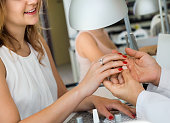 Female client doing nails in nail salon in close-up