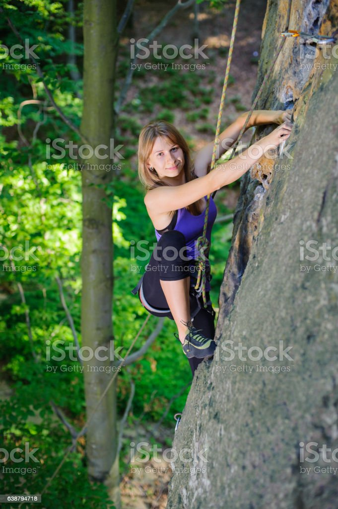 Female climber climbing with rope on a rocky wall stock photo