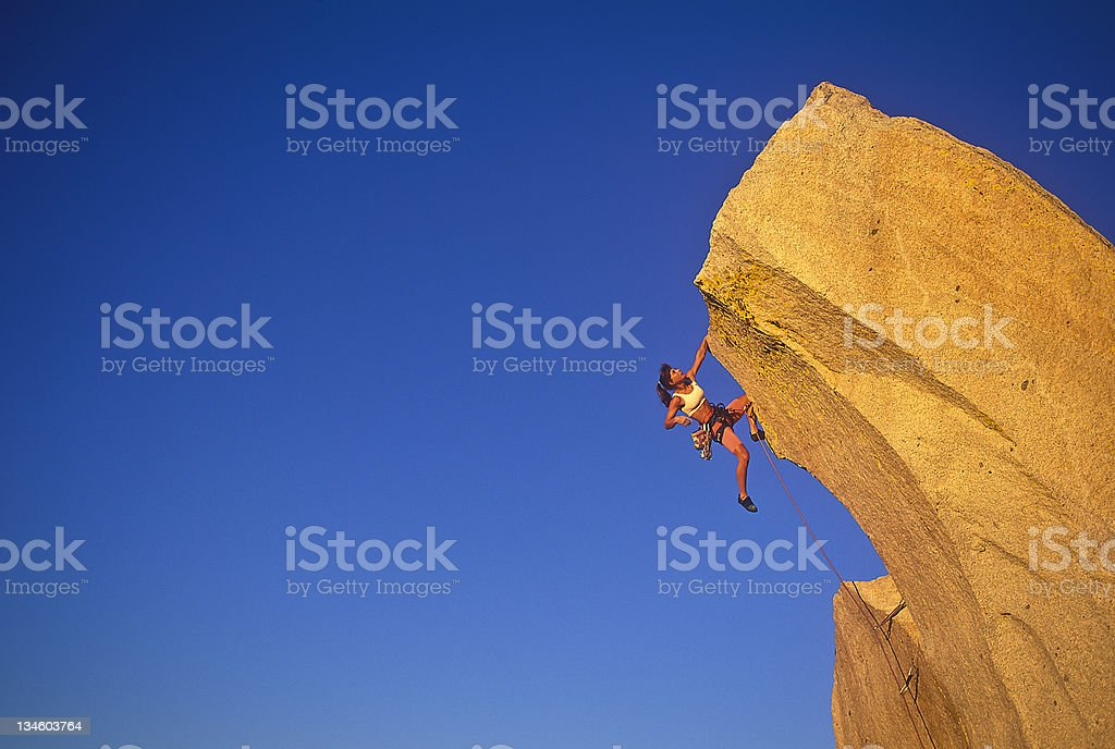 Female climber clinging to the edge. stock photo