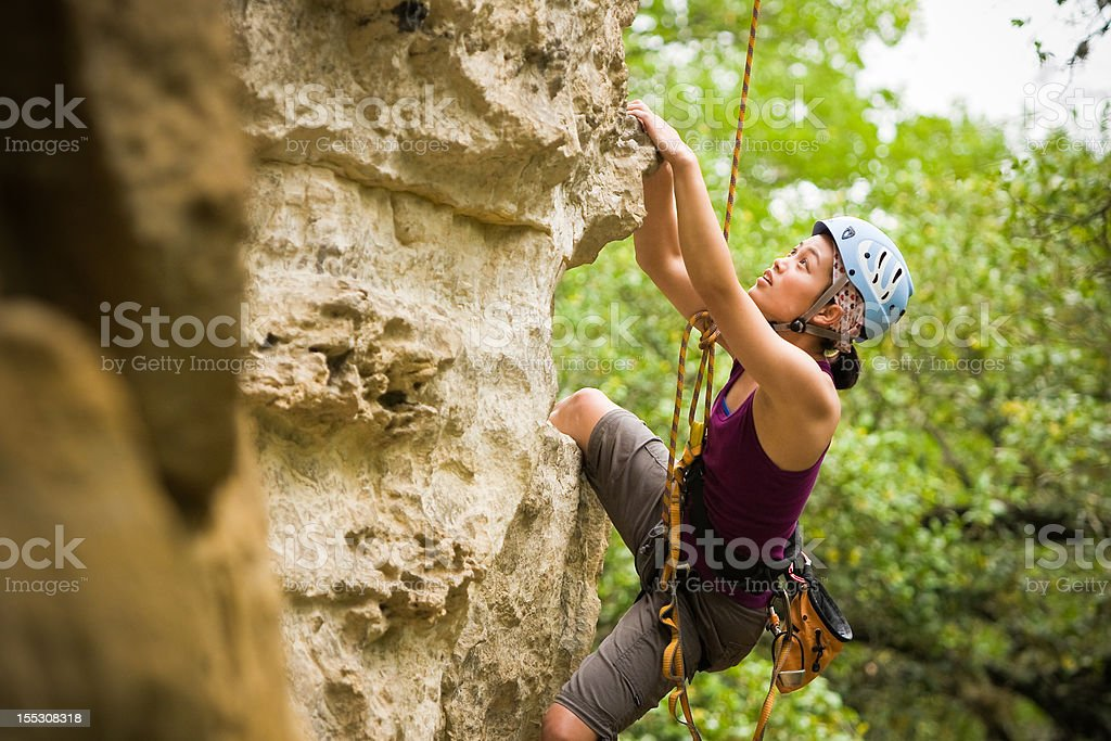 Female climber hanging onto cliff wall royalty-free stock photo