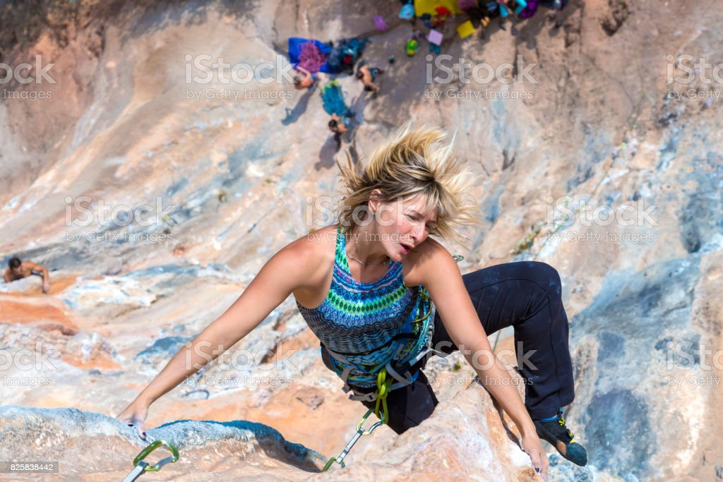 Female Climber makes acrobatic Move on high vertical Rock stock photo