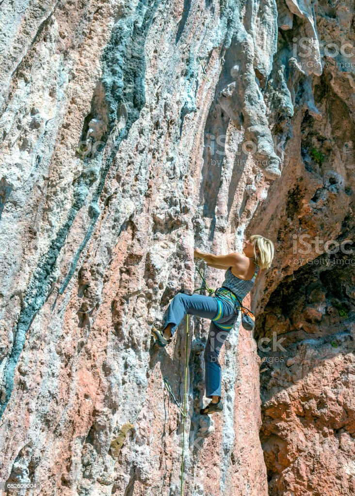 Female Climber moving up on coloгrful overhanging natural Rock stock photo