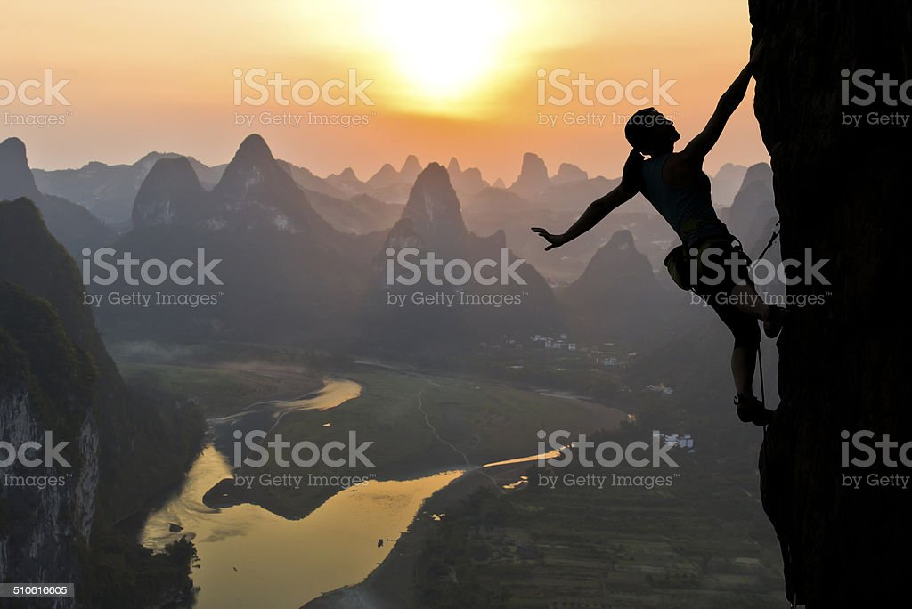 Female climber silhouette against the sunset stock photo