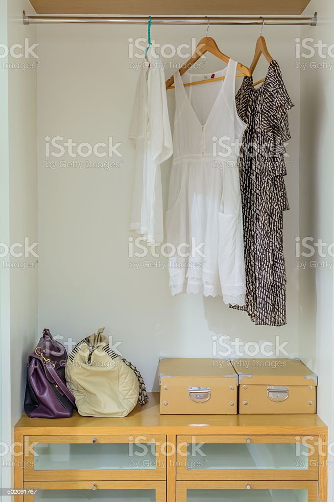 Female clothes on hangers in wardrobe stock photo