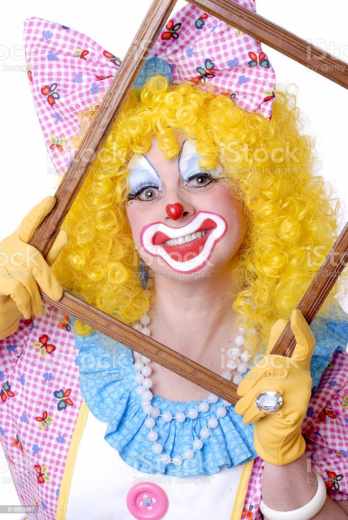 Female Clown Posed Behind a Picture Frame stock photo