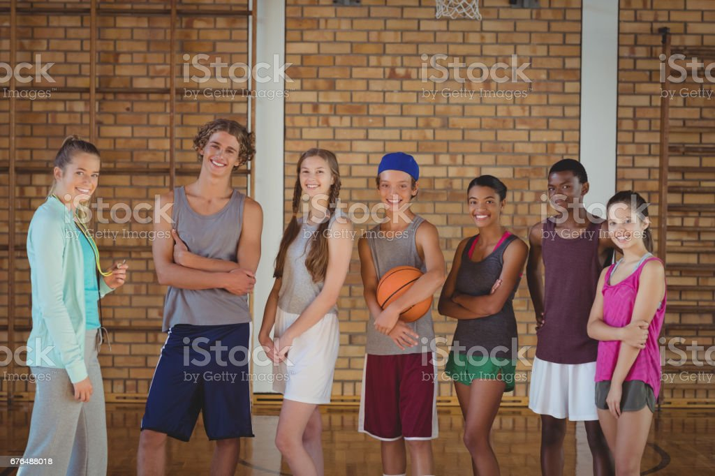 Portrait of female coach and high school kids standing in basketball...
