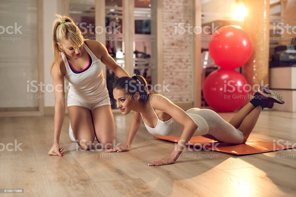 Female coach assisting young woman in doing push-ups. stock photo