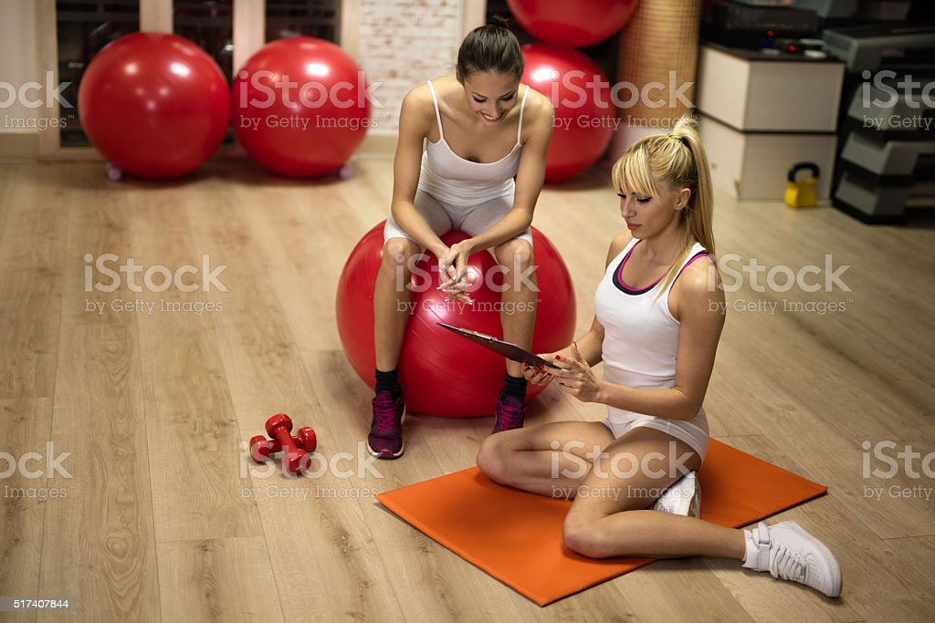 Female coach making an exercise plan with young woman. stock photo