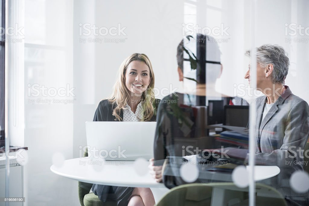 Female colleagues behind glass screen in meeting room stock photo