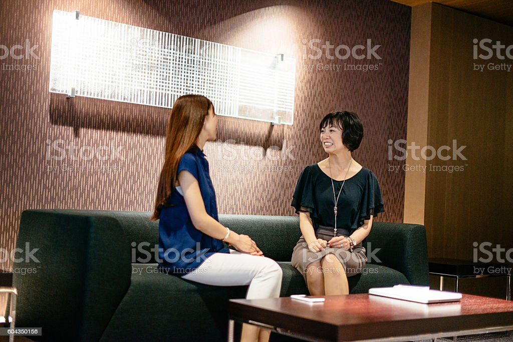 Female colleagues in Japanese company discussing new investments stock photo