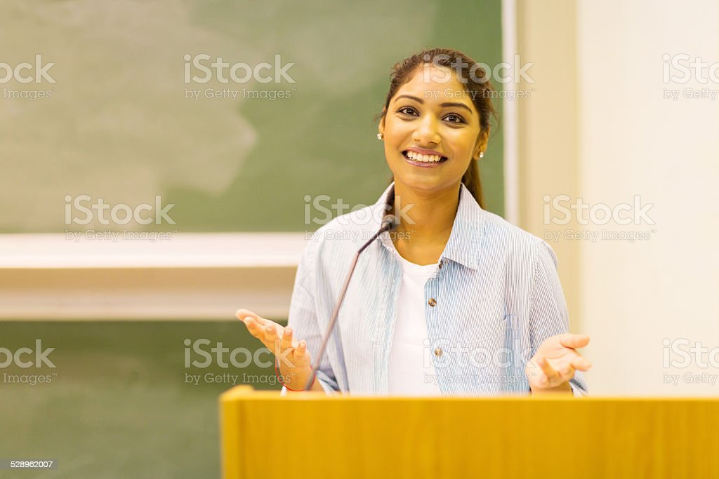 female college student giving a speech to lecture hall stock photo