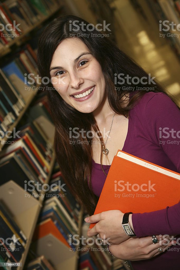 Female College Student Happily Checking out books in the Library royalty-free stock photo