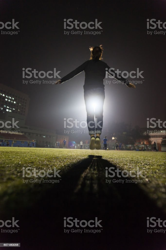 female college student jumping up in the soccer field stock photo