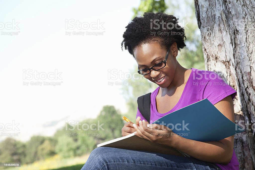 Female College Student Writing in Her Notebook royalty-free stock photo