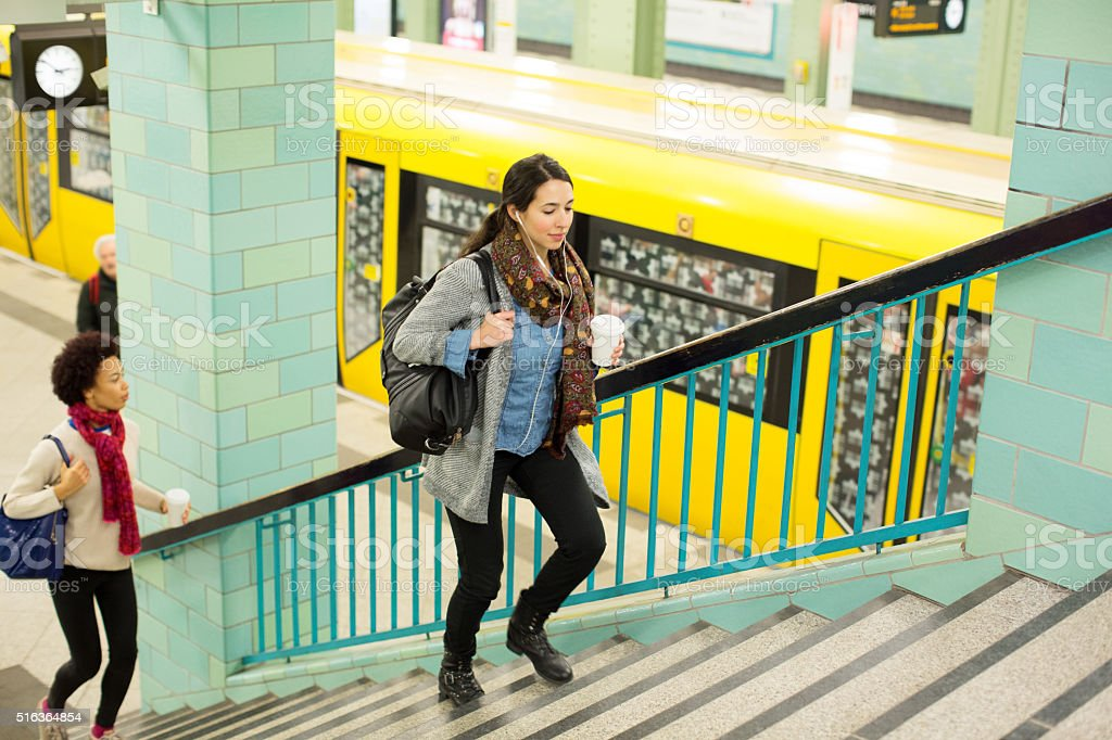 Female commuter with coffee exiting train station stock photo