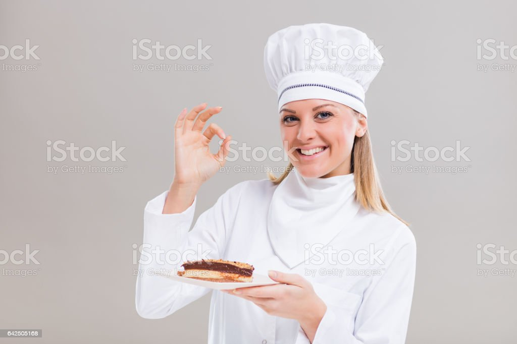 Female confectioner is showing ok sign and holding slice of cake stock photo