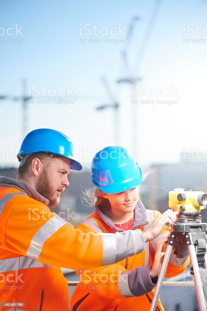 female construction site surveyor and her supervisor using Theodolite stock photo