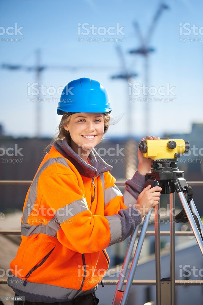 female construction site surveyor looking to camera stock photo