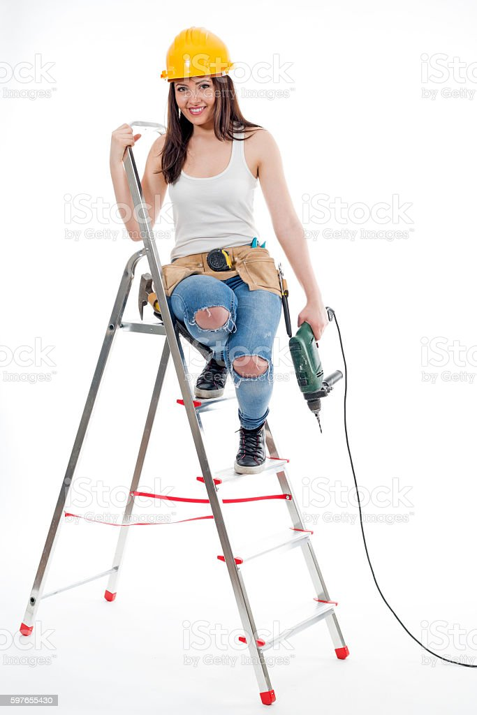 Female construction worker holding a drill, on a ladder stock photo