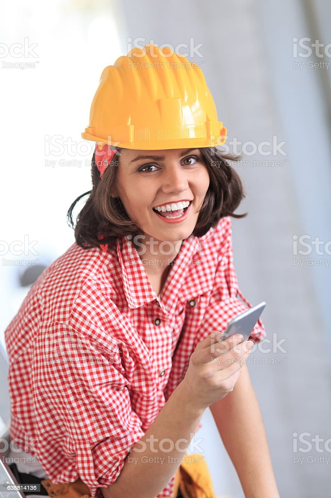 Female construction worker holding smart phone stock photo