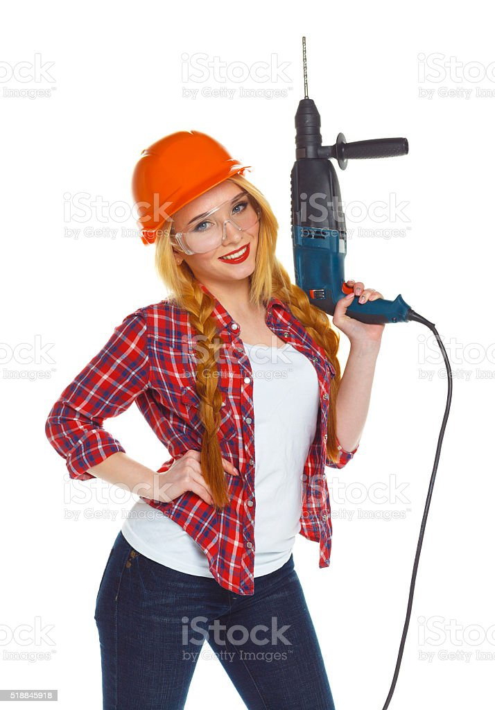 Female construction worker in a helmet with a perforator stock photo