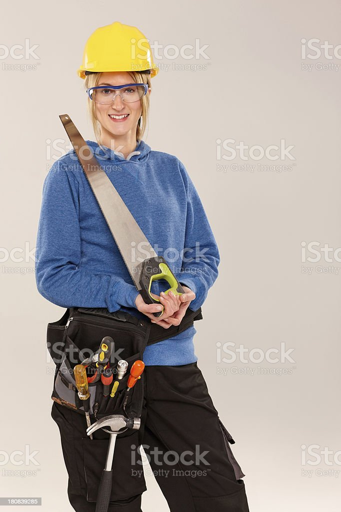 Female construction worker in helmet holding a saw royalty-free stock photo