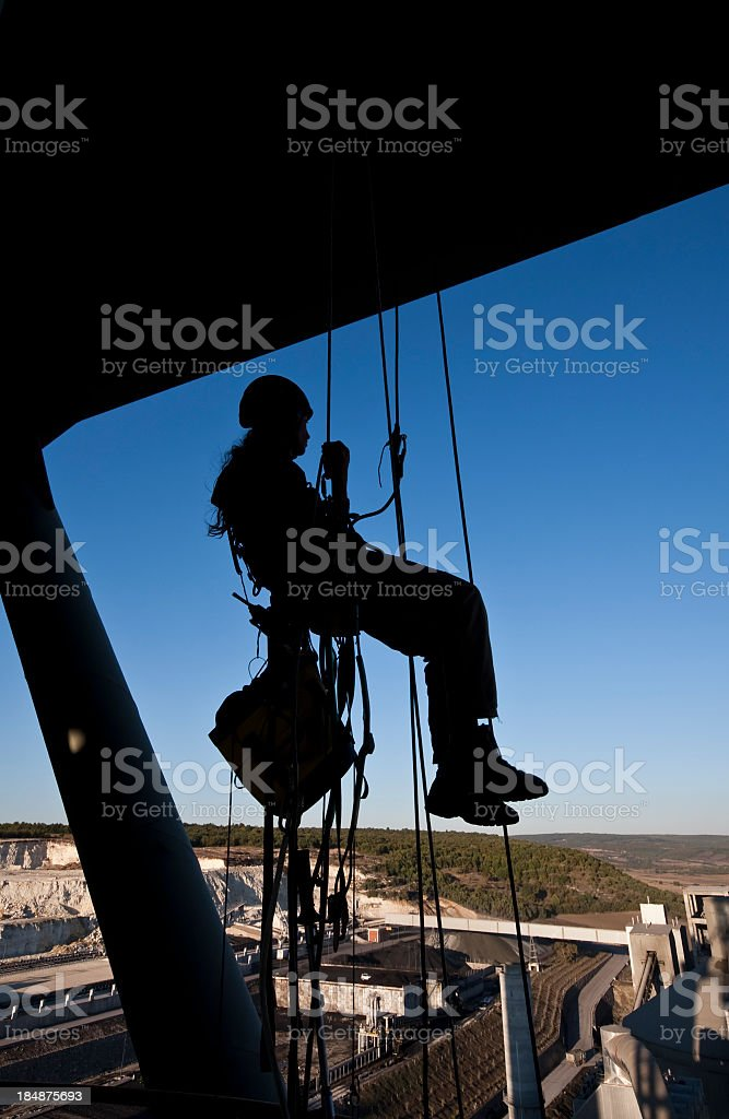 Female construction worker on ropes and pulleys high above stock photo