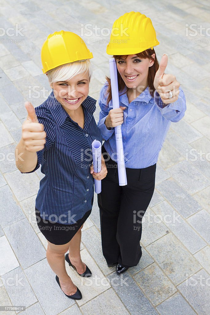 Female constructors making positive thumb gesture while smiling royalty-free stock photo