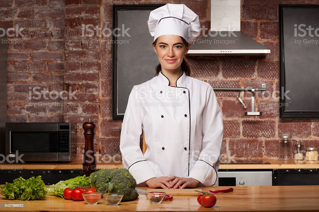 Female cook in a white hat in the kitchen stock photo