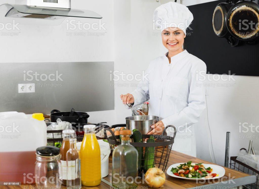 Female  cook wearing uniform working on kitchen stock photo