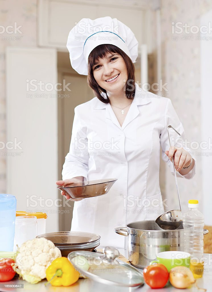 Female cook with ladle pours soup royalty-free stock photo