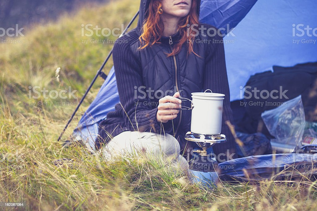 A female cooking with portable gas stove while camping stock photo