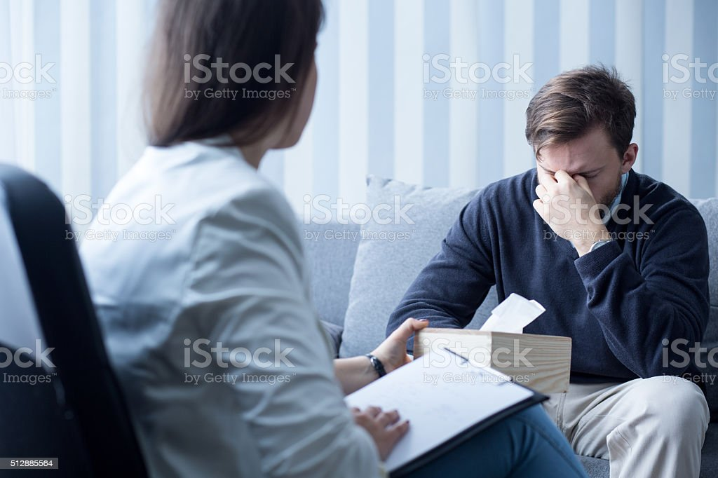 Female counselor helping despressed man stock photo