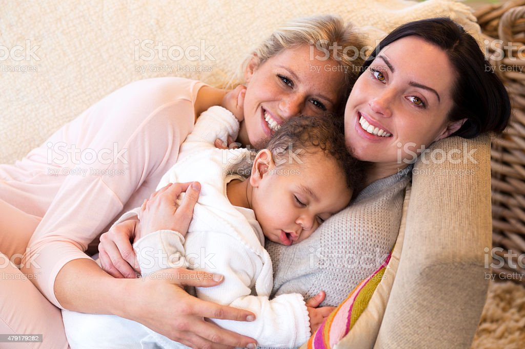 Female couple cuddling with their baby son stock photo