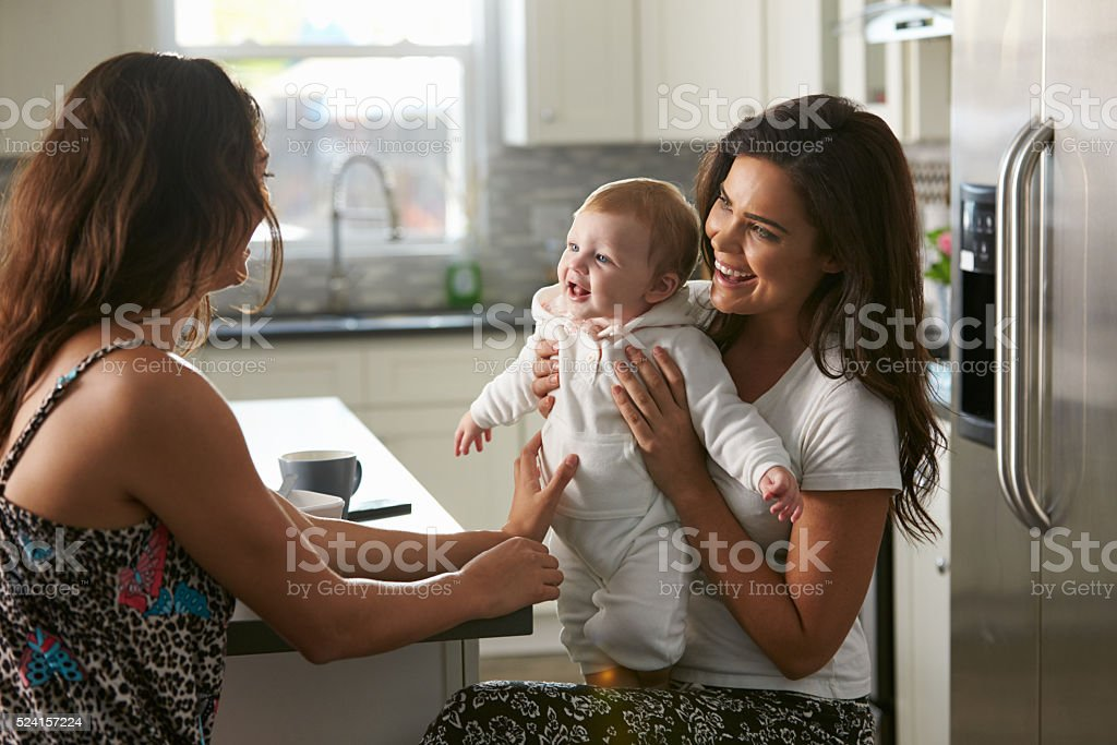 Female couple sitting in the kitchen holding their baby girl stock photo