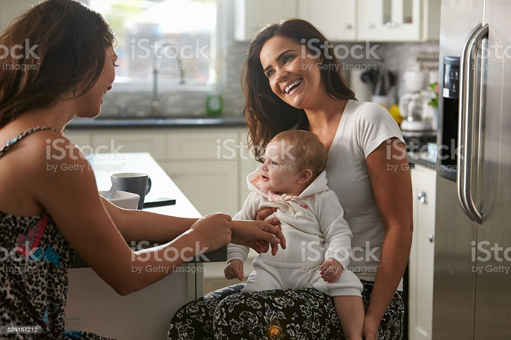 Female couple sitting in the kitchen with baby girl stock photo